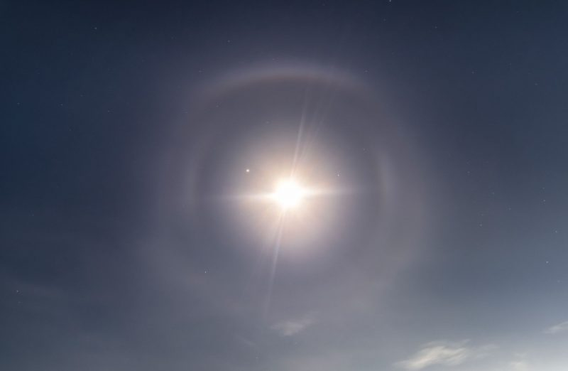 Rare lunar halo: A bright light in the center (the moon) with multiple light rings around it against dark sky.