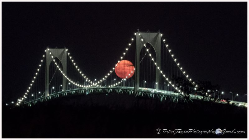 Large, round pink moon seen through a lighted suspension bridge.