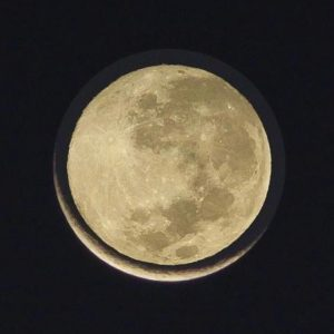A smaller full moon superimposed on a larger crescent moon.