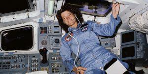 Woman astronaut in blue NASA uniform floating inside space shuttle control cabin.