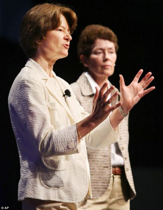 Two middle-aged women side by side, one gesturing with both hands.