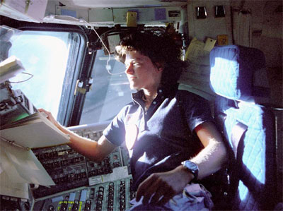 Sally Ride in NASA uniform in space shuttle by window with sunlight.