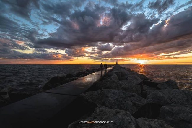 Perspective view of dark clouds over bright sunset, long pier running towards the horizon.