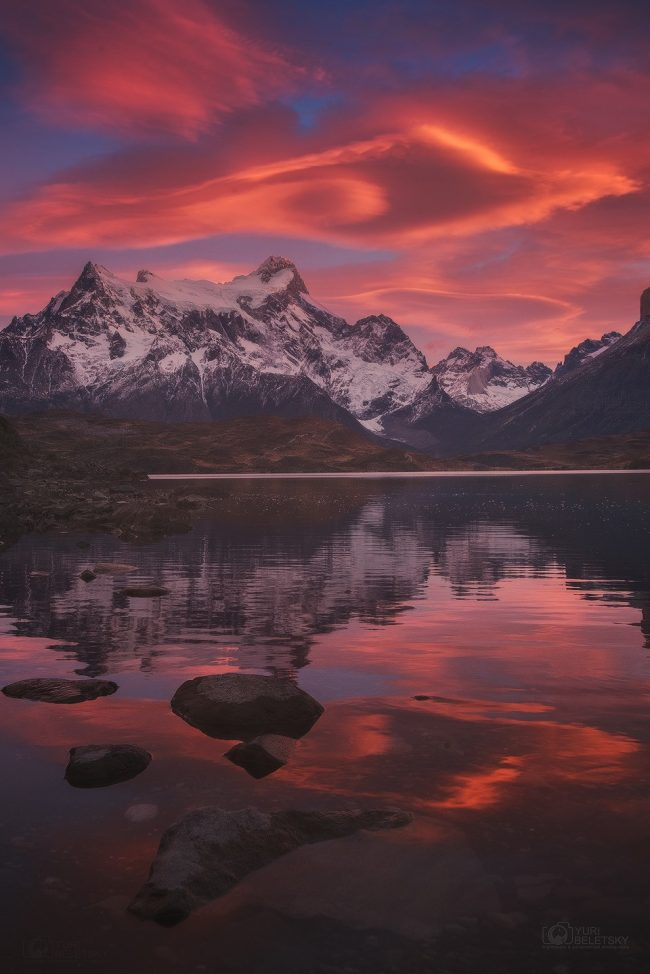 Swirling dark-pink clouds over rugged snowy mountains, reflected in lake.