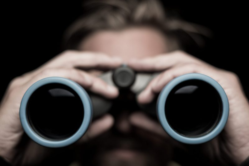 The front of a pair of binoculars being held up in front of a person's face.