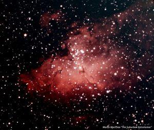 Reddish nebula with many stars in background.