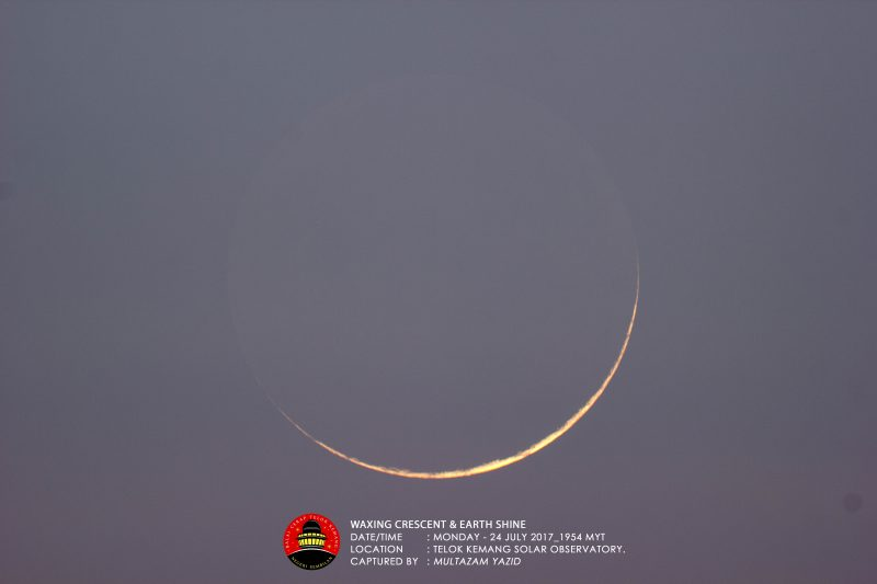 Large, very thin, yellowish crescent against a blue-gray sky.