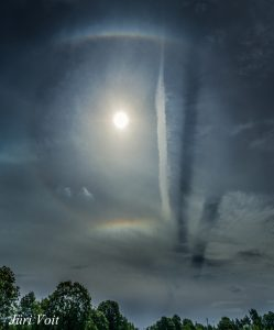 Bright light (sun) in top center, with a halo and a jet contrail with two shadows on its right side.