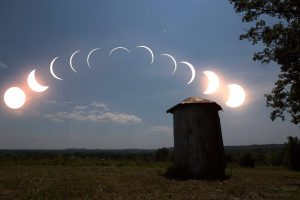 Arc of 11 crescent suns from wide to narrow to wide in sky above small outbuilding.