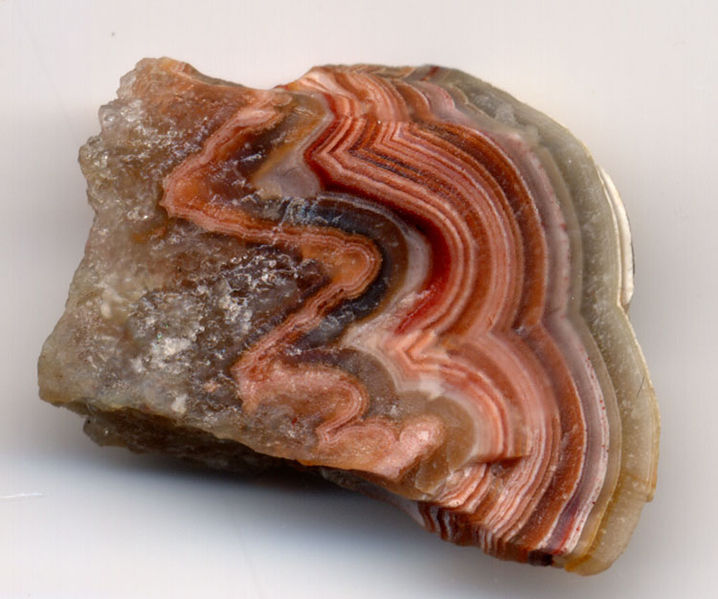 Polished rock surface with parallel red and pink arc-shaped bands.