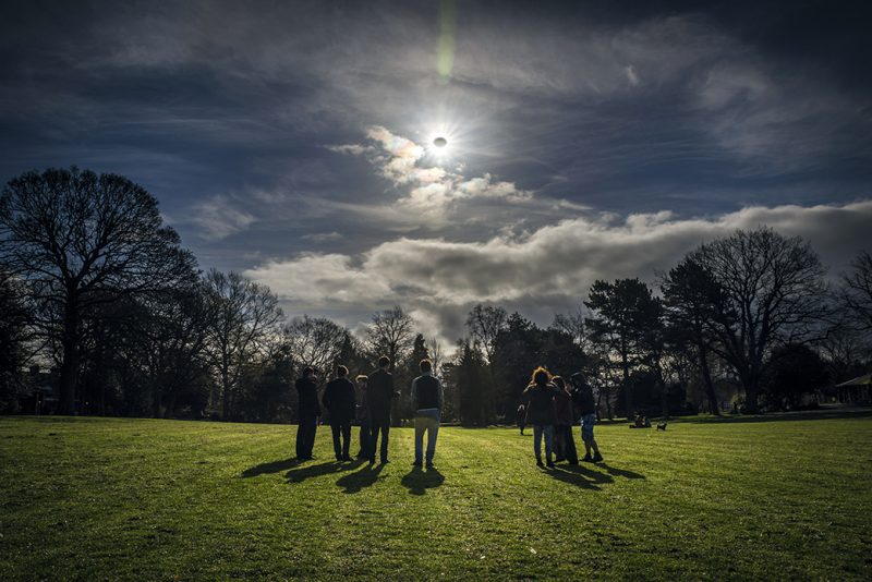 Seven people on green field with trees in background and solar eclipse above.