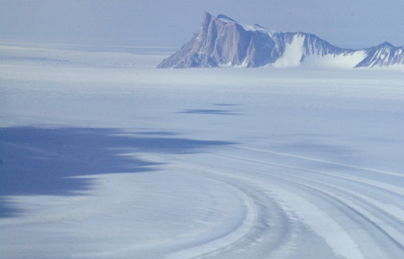 Wide sheet of flat ice with pointy, bare, rocky mountains in background.