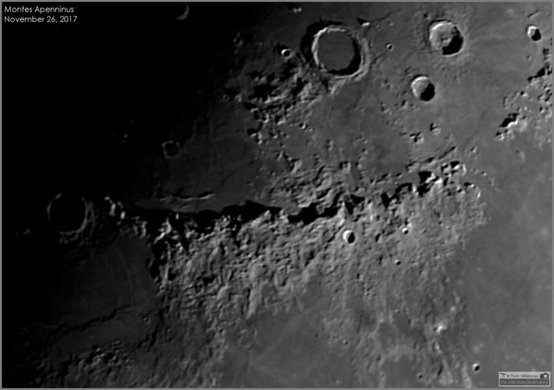 Telescopic closeup of band of mountains on moon with a few large craters.
