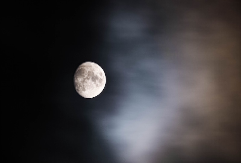 International Observe the Moon Night: A sphere, gray and white, shines in a black night sky half-clouded with pale fog.