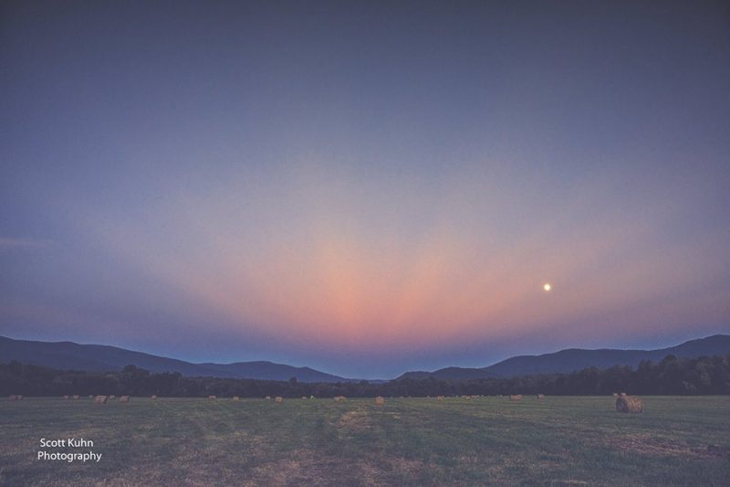Faint pink rays converging to a point above low twilit hills.
