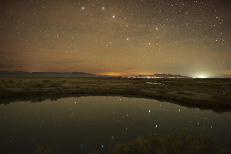 Big Dipper in lightish sky, reflected in a calm lake.
