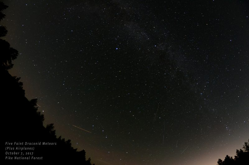 Starry sky with faint Milky Way and short bright streaks.