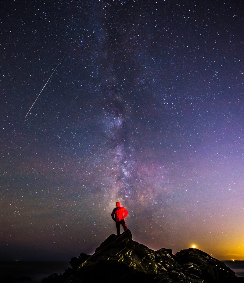 Man standing on a peak beneath starry sky with cloudy Milky Way and a white streak.
