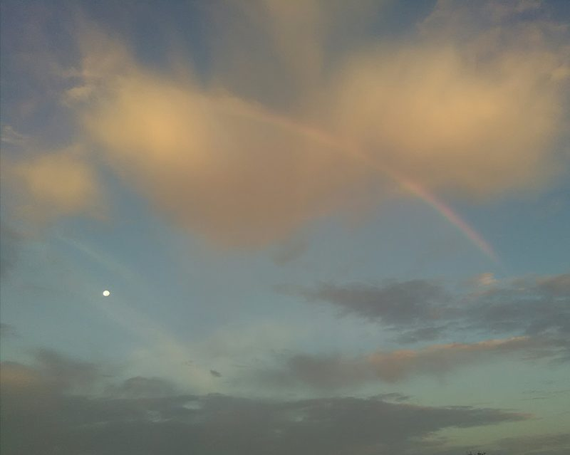 Daytime moon between torn clouds under the arc of a wide, high rainbow.