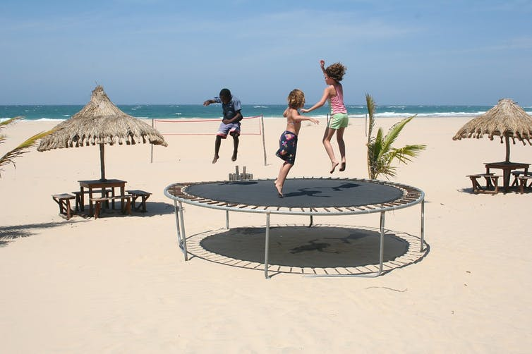 Three children jumping on a round above-ground trampoline at the beach.