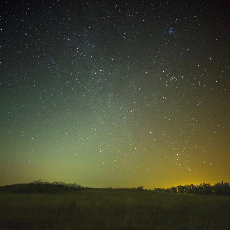 Starry sky with wide, fuzzy triangle of light sticking up from the horizon.