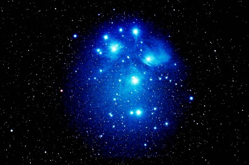 Roundish patch of bright glowing blue with stars in it against starry background.