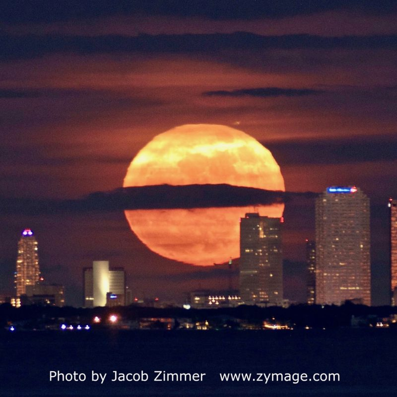 Full moon rising over a city.