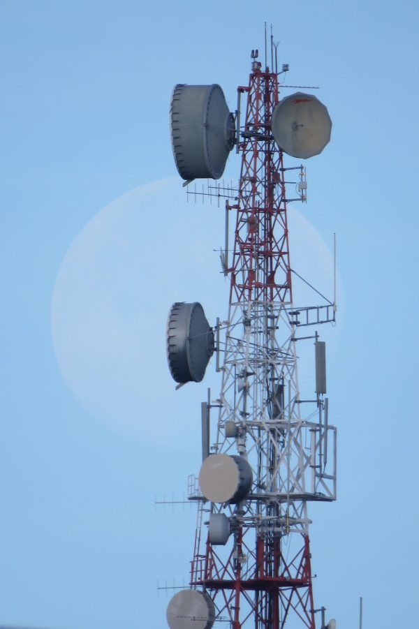 Enormous, faint moon behind radio tower with lots of antennas on it.