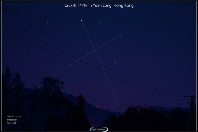 Night sky above dark trees, with lines between stars showing cross-shaped constellation.