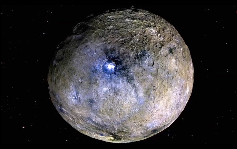 Gray, round, rocky Ceres, with 2 headlamp-like bright spots visible within one of its craters.