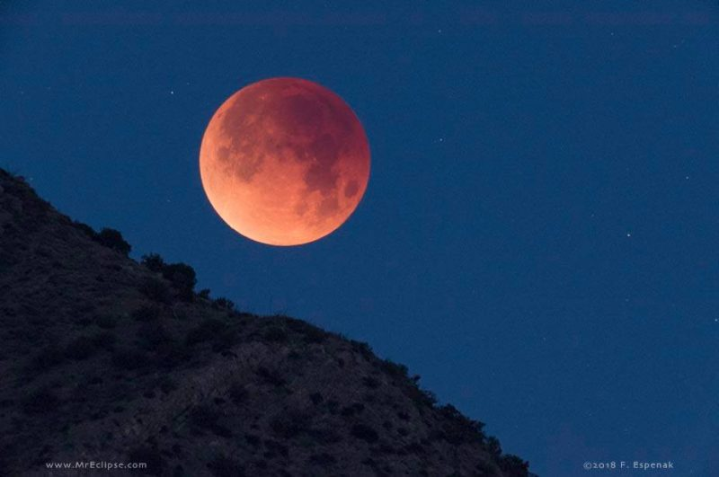 Giant red-orange eclipsed moon over steep brushy hillside.