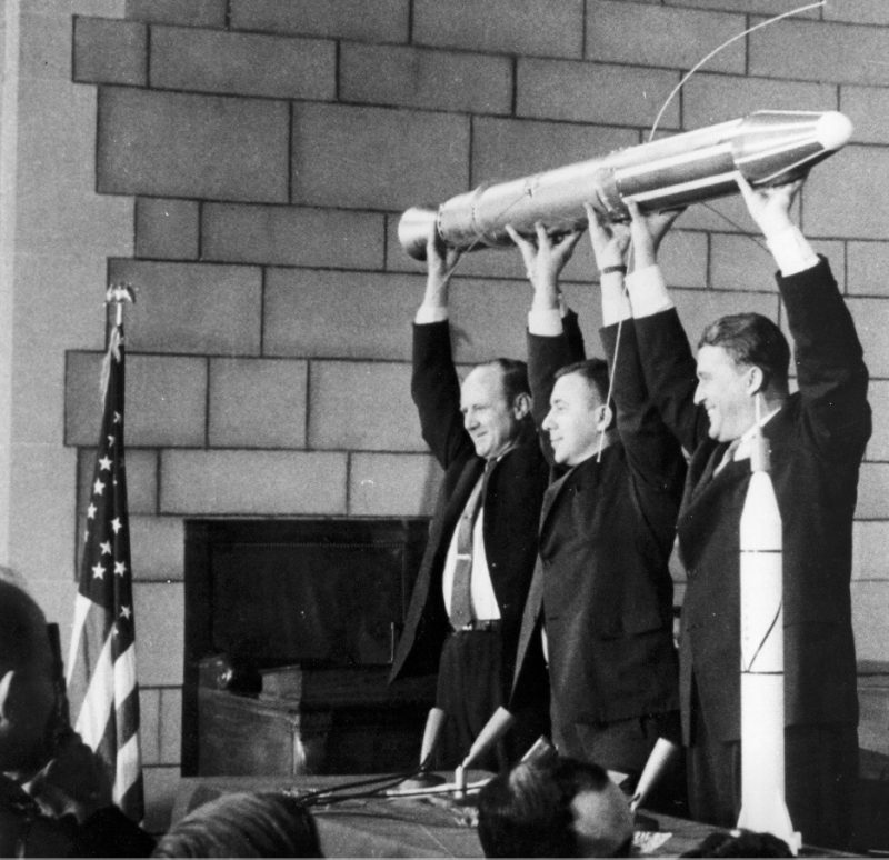 Three men in suits holding a rocket over their heads.