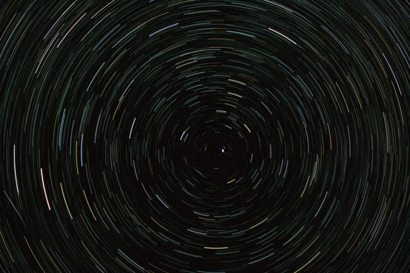 Short streaks of light in concentric circles against a black background.