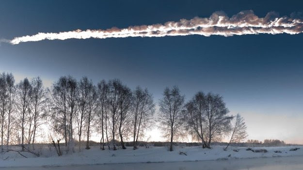Bright white smoke trail above bare trees in snowy landscape.