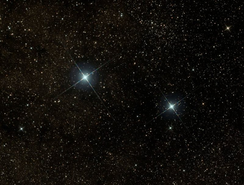 Photo showing two bright blue stars against a backdrop of very many fainter white stars.