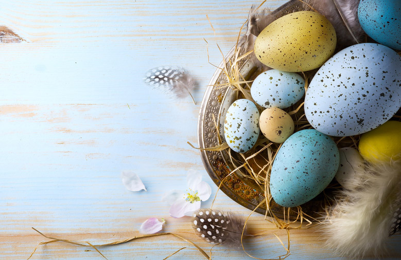 A basket full of naturally colored speckled birds' eggs, yellow, blue.