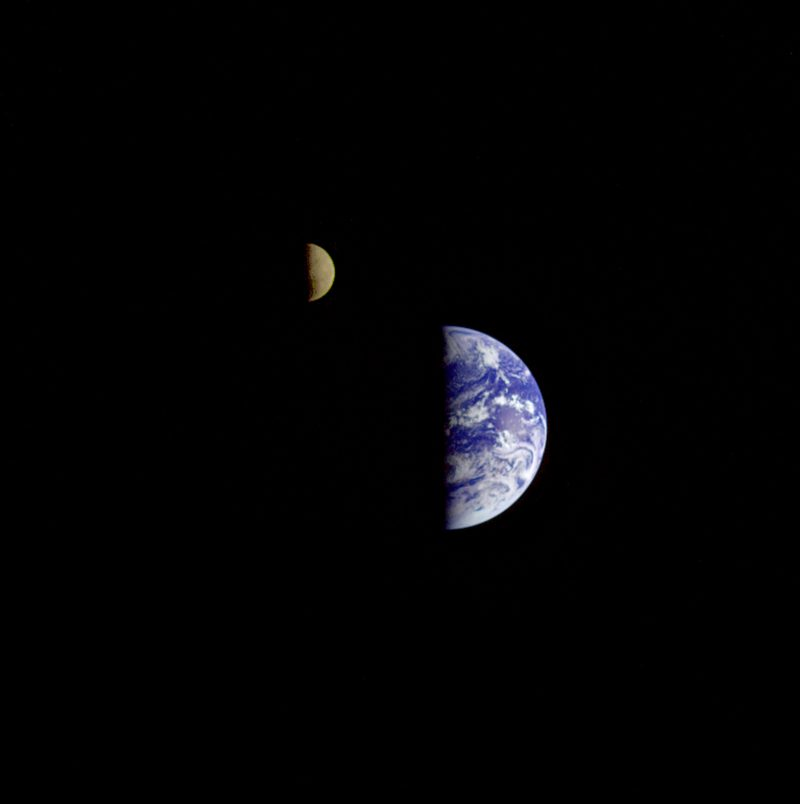 Brownish moon above bright blue and white Earth both in quarter phase, meaning half-lit.