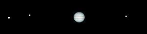 Panorama of Jupiter with 3 star-like dots on black background.