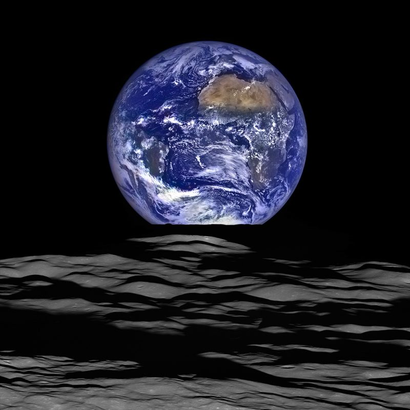 Full blue and white Earth viewed past hilly gray lunar landscape.