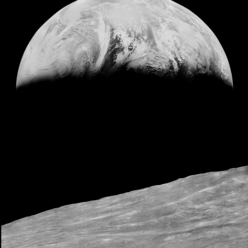 Black and white photo, lunar surface in foreground and crescent Earth above.