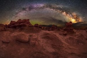 Starry arc of Milky Way, rising over a red rocky landscape.