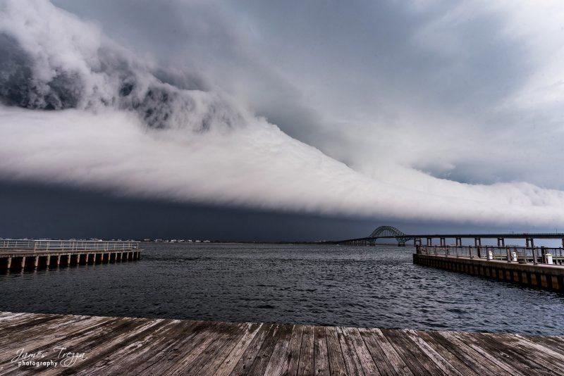 Shelf cloud with turbulent top under gray sky.