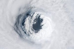 Huge swirling mass of white clouds with dark hole in center.