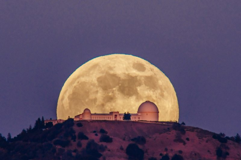 Gigantic moon rising behind cluster of pink buildings with domes on a hilltop.