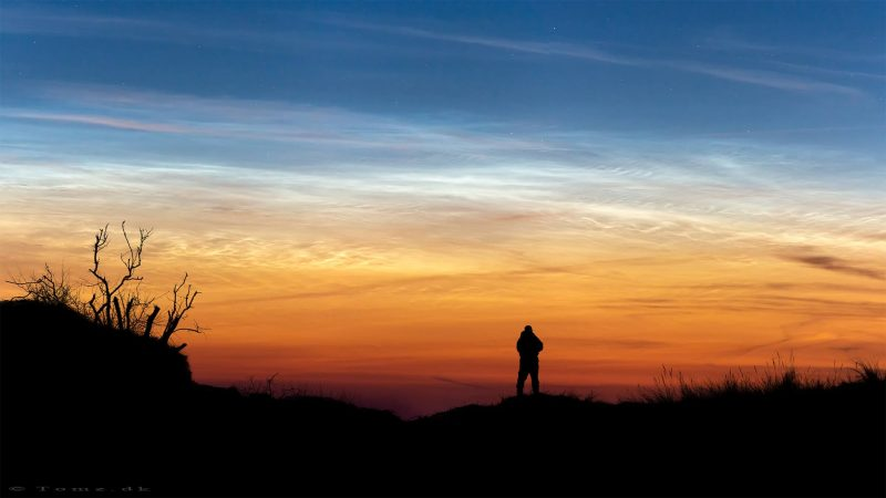 Man silhouetted against sunset sky with noctilucent clouds above.