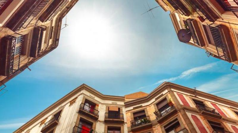 Looking straight upward between three old-fashioned buildings, bright white glowing sun in blue sky.