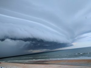 Bowed shelf cloud moving over a beach and ocean.