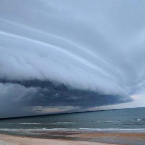 Layers of shelf-like linear clouds below a thunderstorm.