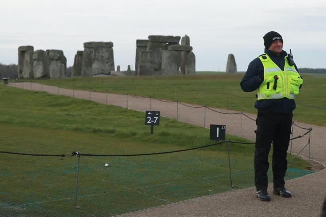 Guard standing next to rope fence with Stonehenge's standing stones in the distance.