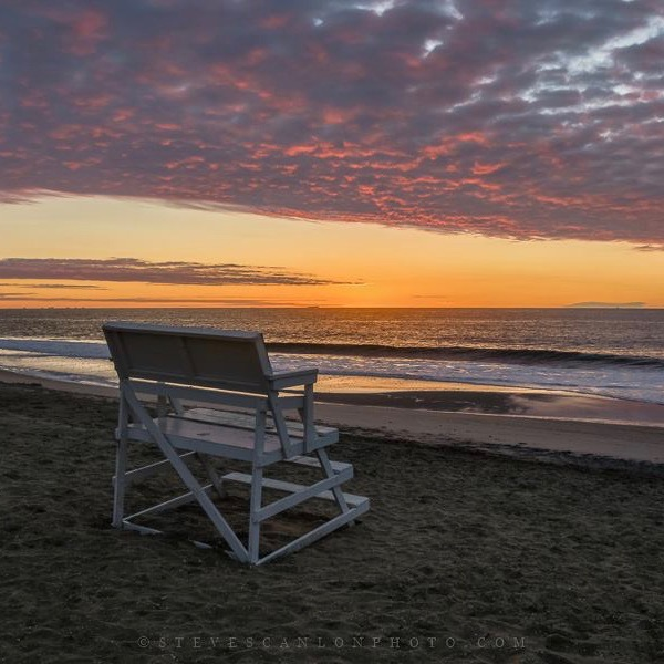 Sunrise by the ocean. A bench sitting on the shore under pink clouds.
